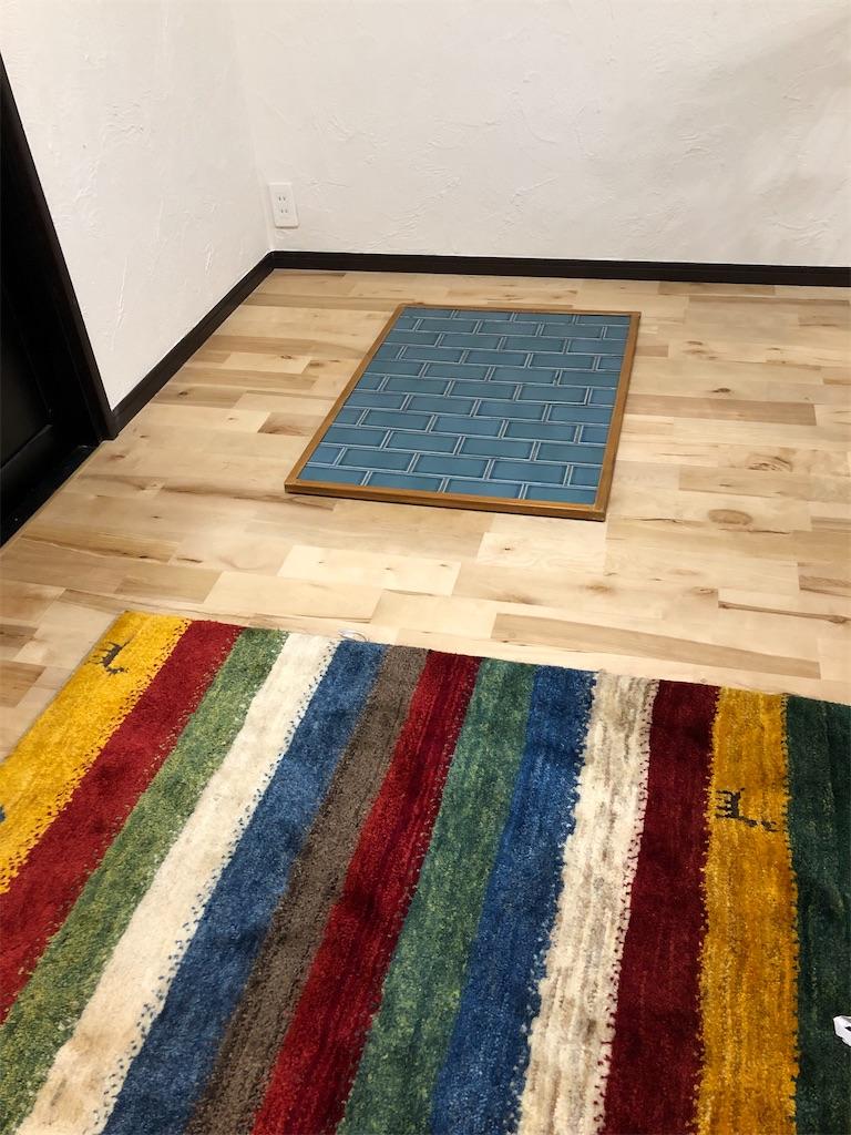 無垢材の床に置かれたギャッベと炉台