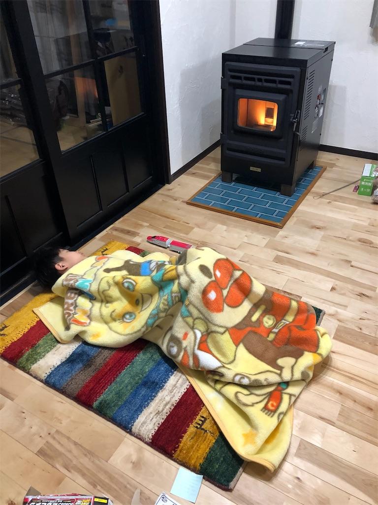 ギャッベに寝転び毛布を被る子供