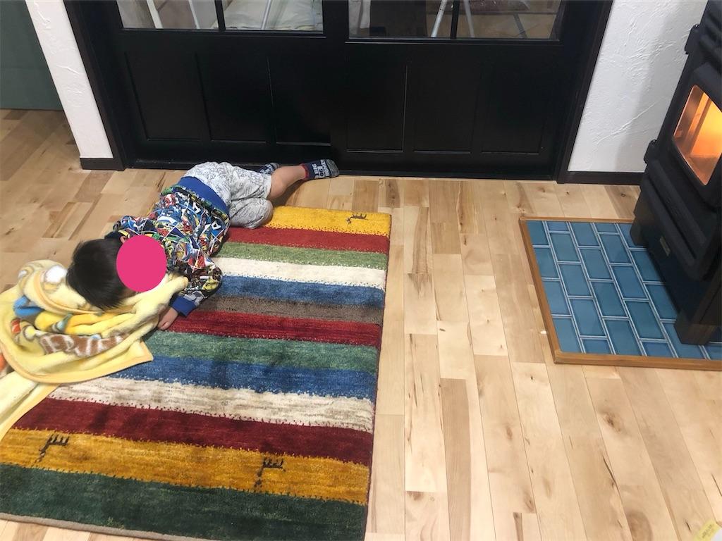 毛布にしがみつきギャッベの上で寝ている子供