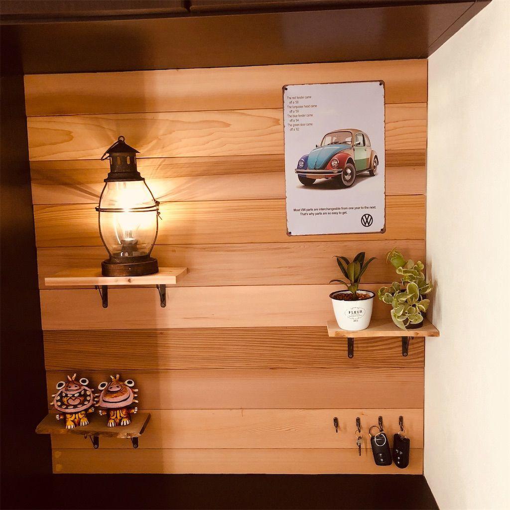 ビンテージ風ランタンとビートルのブリキ看板と植物で飾られたカフェ風の壁
