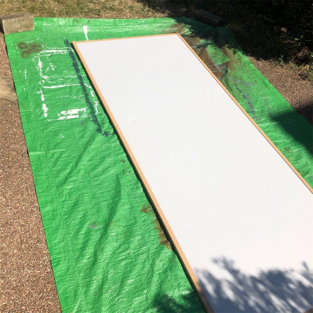 グリーンシートの上に置かれた塗装前の白い襖