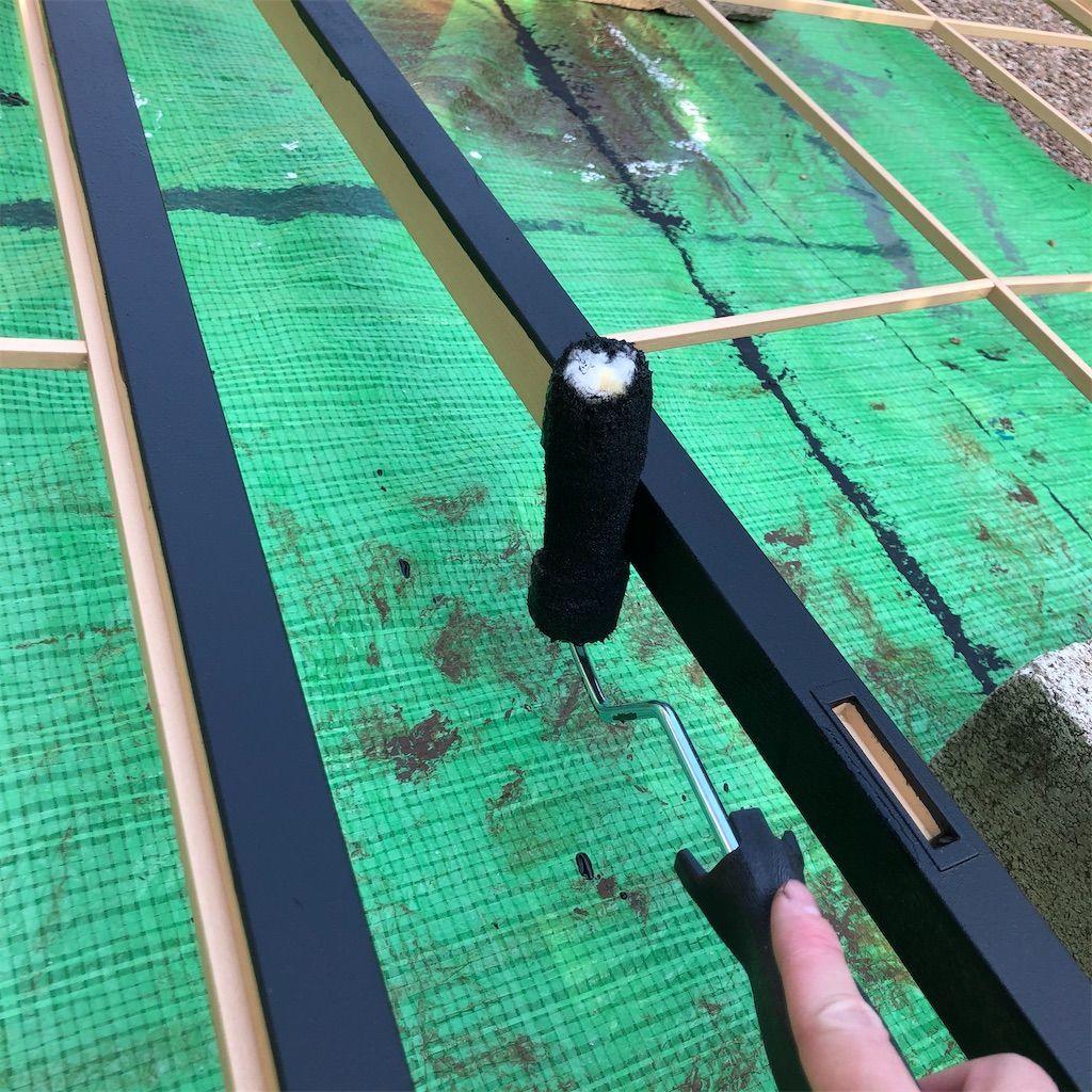 ローラーを使って水性塗料で黒く塗られていく障子枠