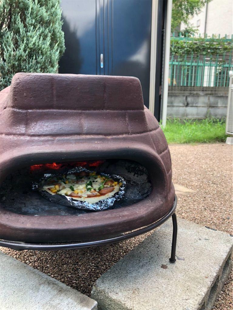 チムニーピザ窯でピザを焼いている図