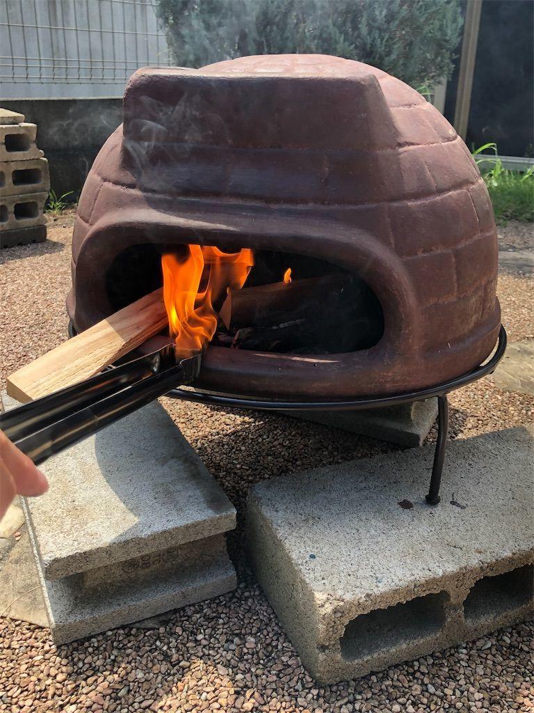 炎に包まれるチムニーピザ窯の中の薪