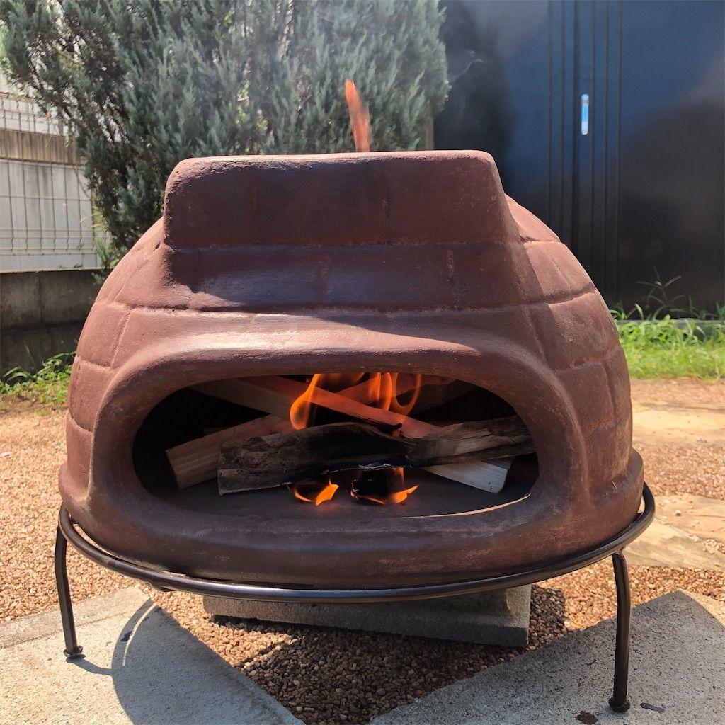 チムニーピザ窯の中の薪をトングで動かす