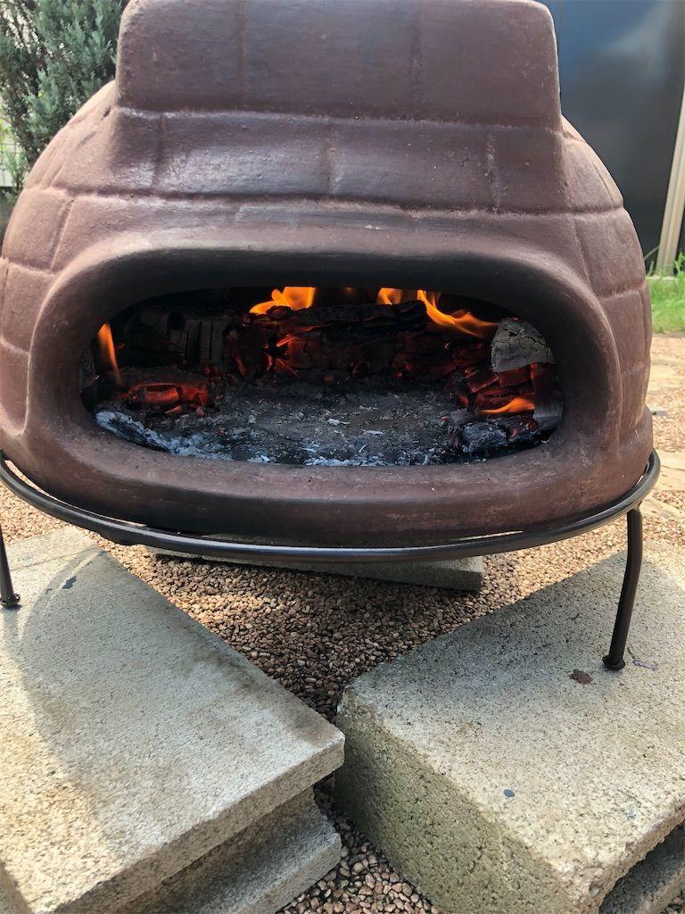 チムニーピザ窯の中の薪を奥に寄せてピザを置くスペースを作った