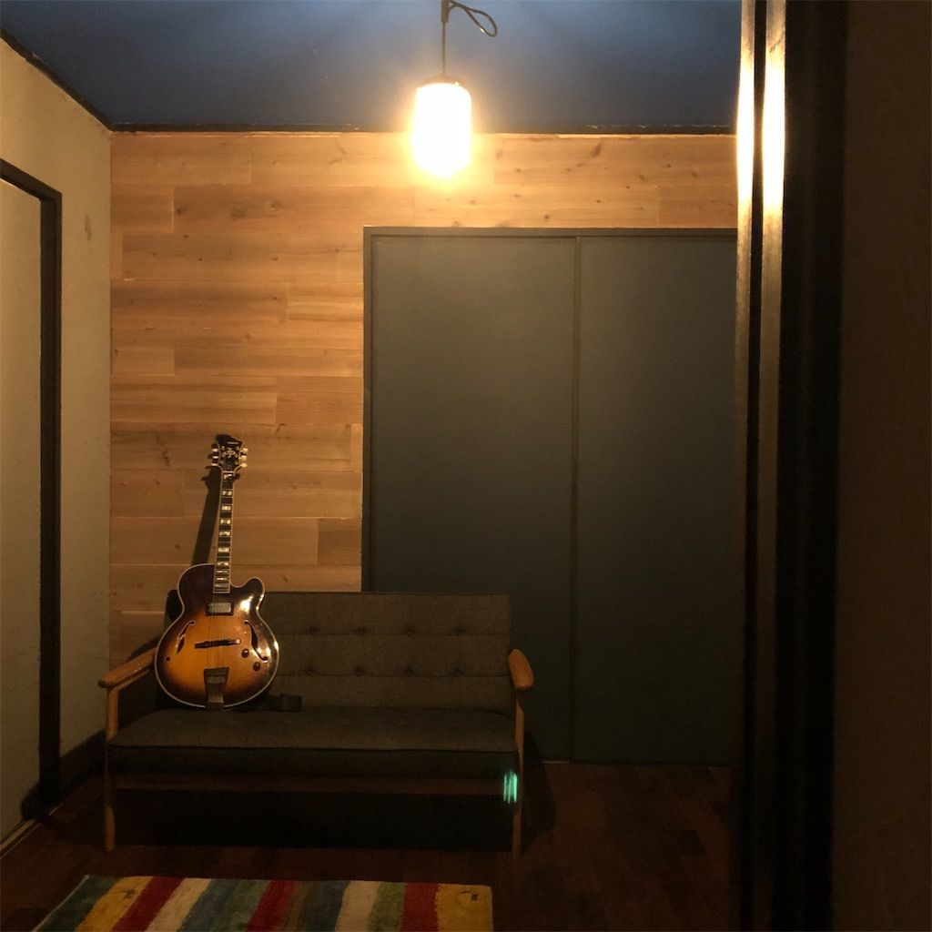 青い天井。壁紙張り替え。バー風の雰囲気を意識した暗めの照明とソファとギターのある部屋。