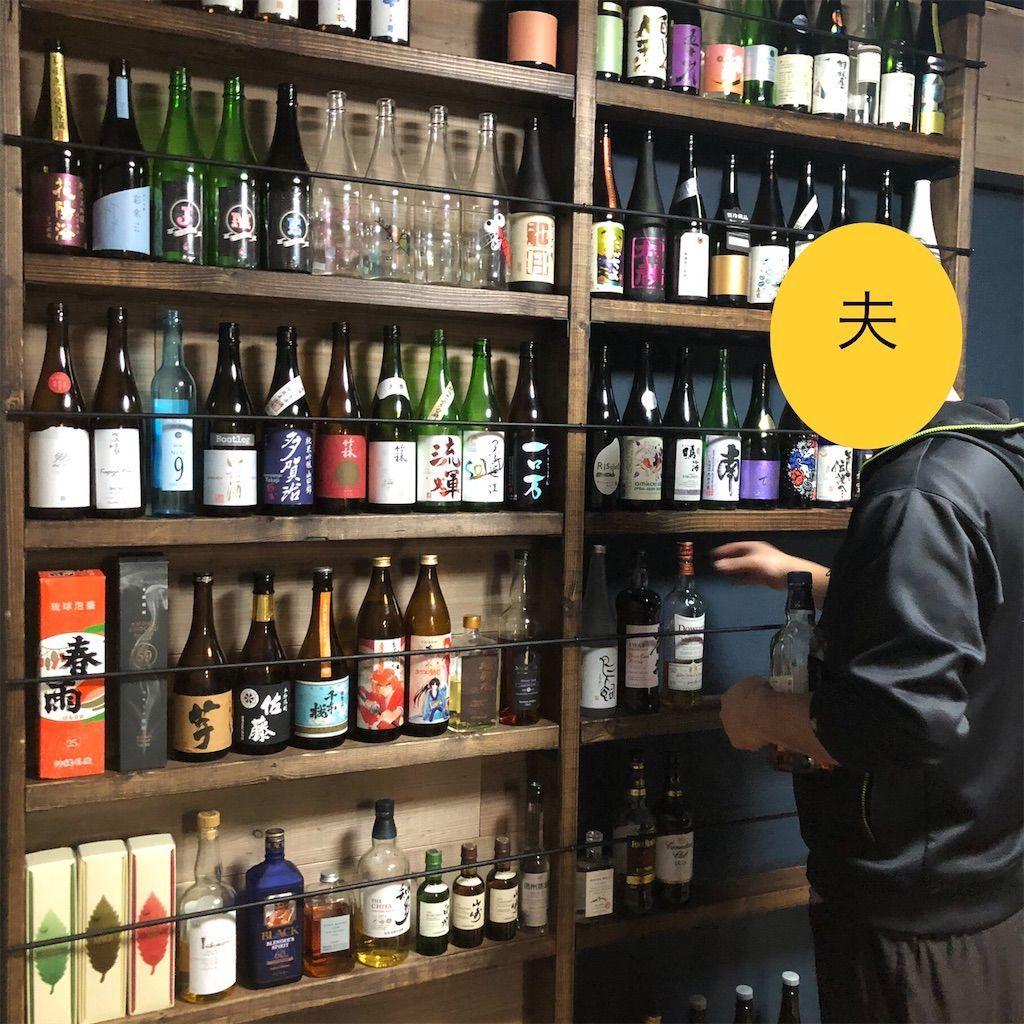 2×4とラブリコで作った酒棚に瓶を並べる夫