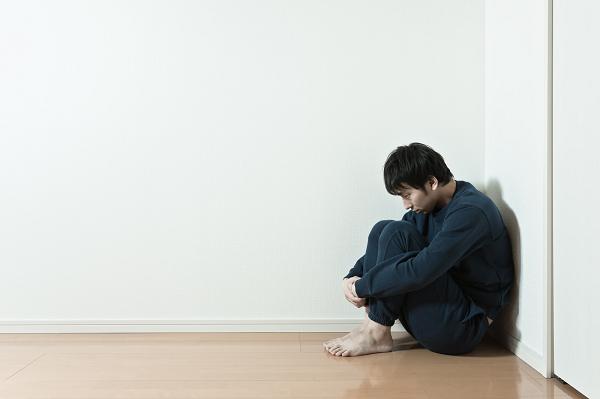 部屋の隅にうずくまり後悔する男性