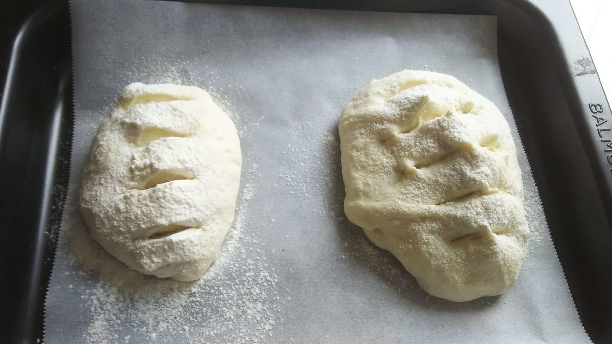 成形したパン生地に化粧粉をかけクーぷを入れる