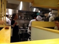 [銀座][ラーメン]白木のコの字型カウンター奥の厨房で、和帽子と白衣に身を包む従業員