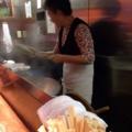 [桜木町][日ノ出町][ラーメン]常連客と談笑しつつも慣れた手つきで麺揚げするおばちゃん