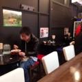[麻布十番][ラーメン]L字型カウンター7席、壁沿いに2名掛け黒テーブル3卓の計13席