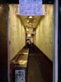 [大阪][なんば][千日前][ラーメン]びっしりサインの両壁の奥に見える8席のカウンター