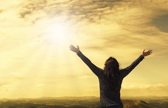 雲間に見える太陽に向かって両手を上げる女性