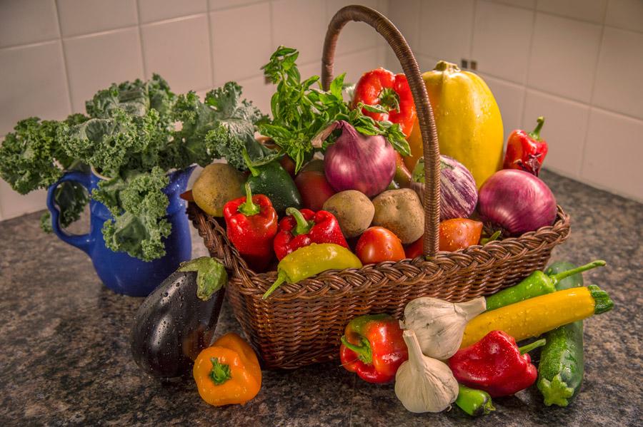 美味しそうな色とりどりの野菜が台所にカゴに入れて置かれています。