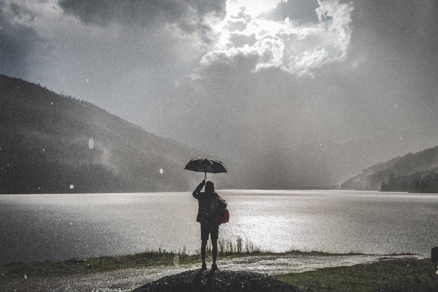 傘を差す人が見上げた先では、雨雲の隙間から日の光がのぞいています。