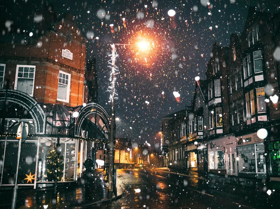 雪が降りしきるレンガの建物が並ぶ街並みです。