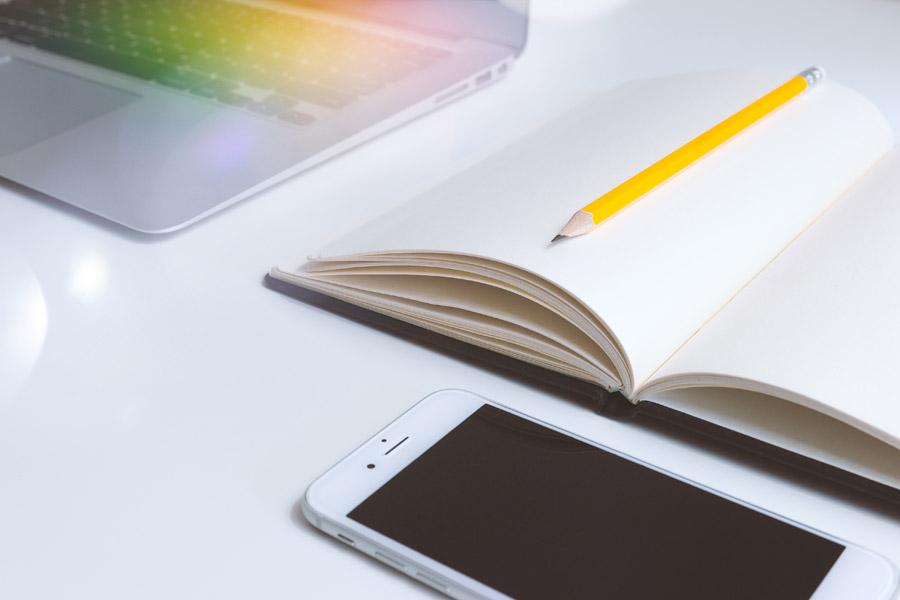 スマホと紙のノート、ノートパソコンが写った写真です。