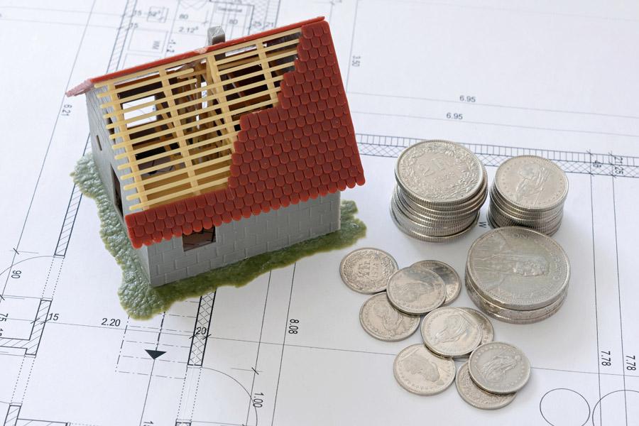 家の模型と硬貨の写真です。