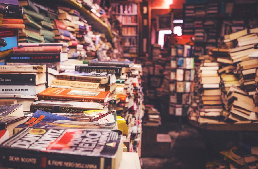 乱雑に本が積み上げられている本屋の写真です。