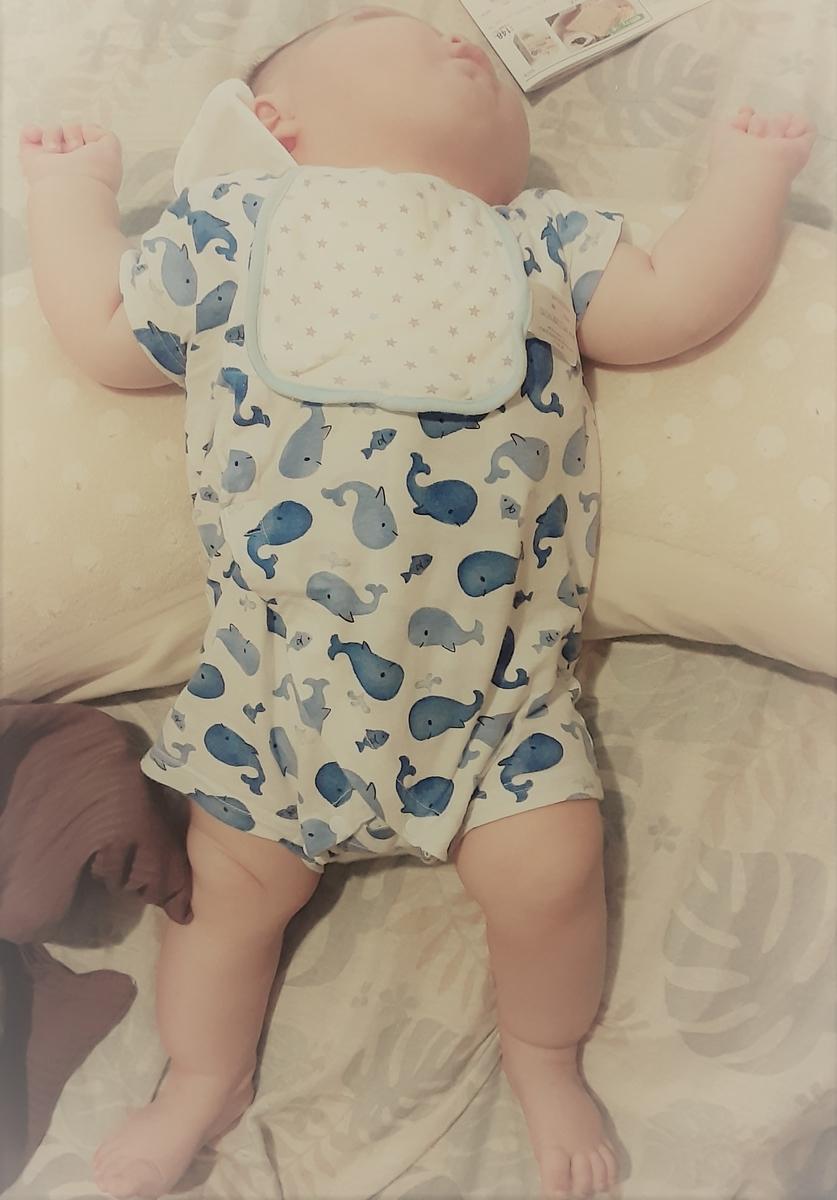 クッションに首をのせてのけぞっている仰向けの赤ちゃんの写真です。