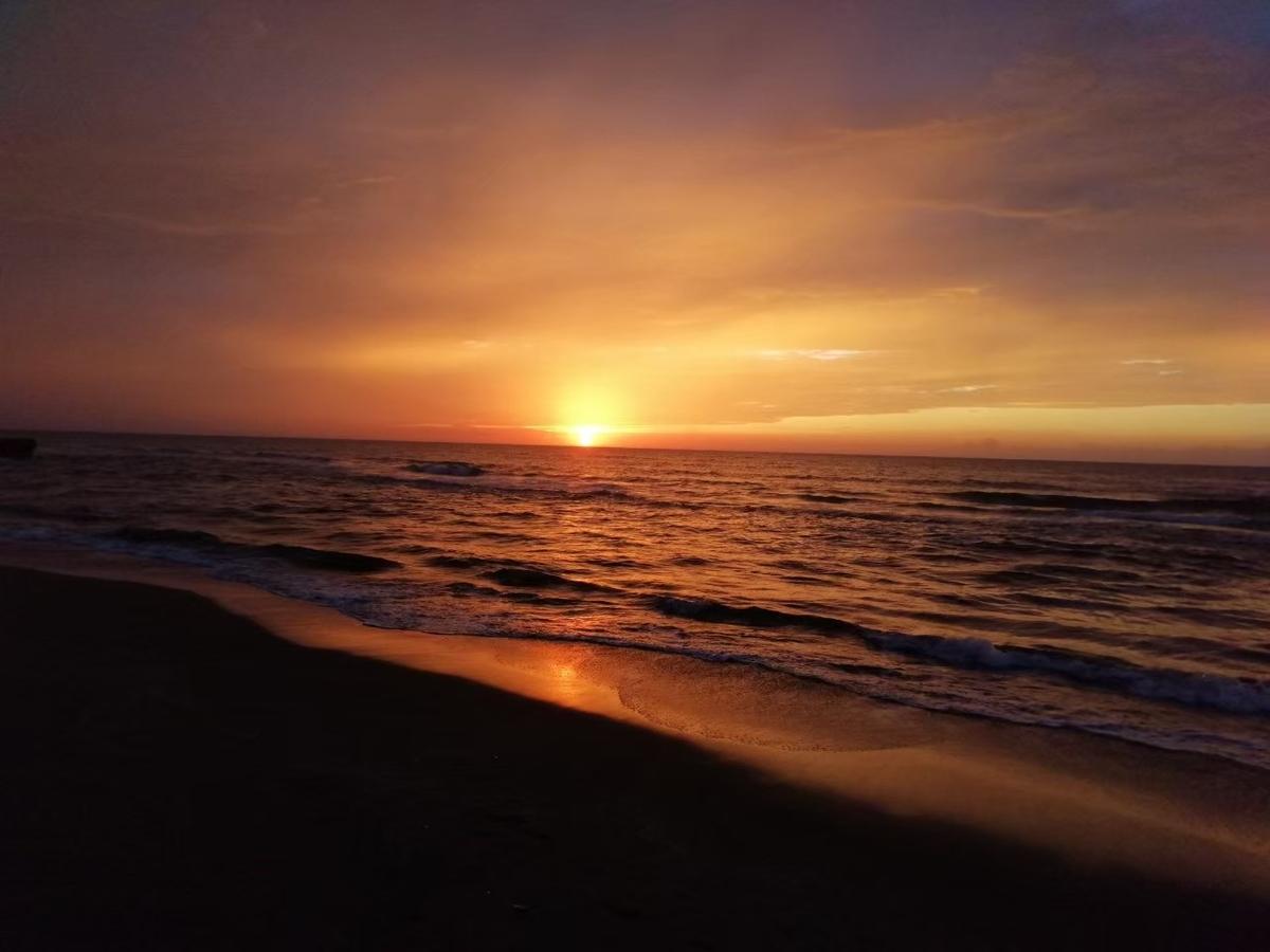 水平線の向こうの雲の合間から、太陽が昇る様子を浜辺から撮影した写真です。