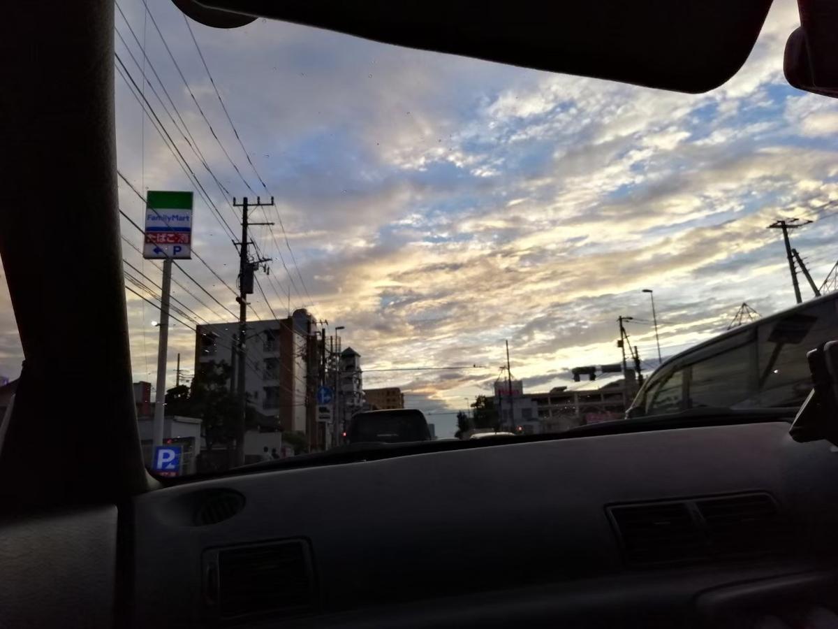 車の窓から青い空に黄色がかった夕日を反射した白い雲が浮かんでいます。