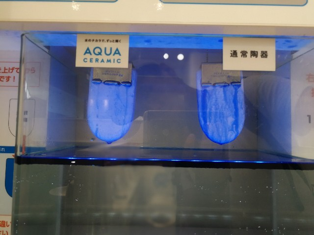 AQUA CERAMICと通常の陶器に汚れ(青い液体)を付着させ水の中に入れる。