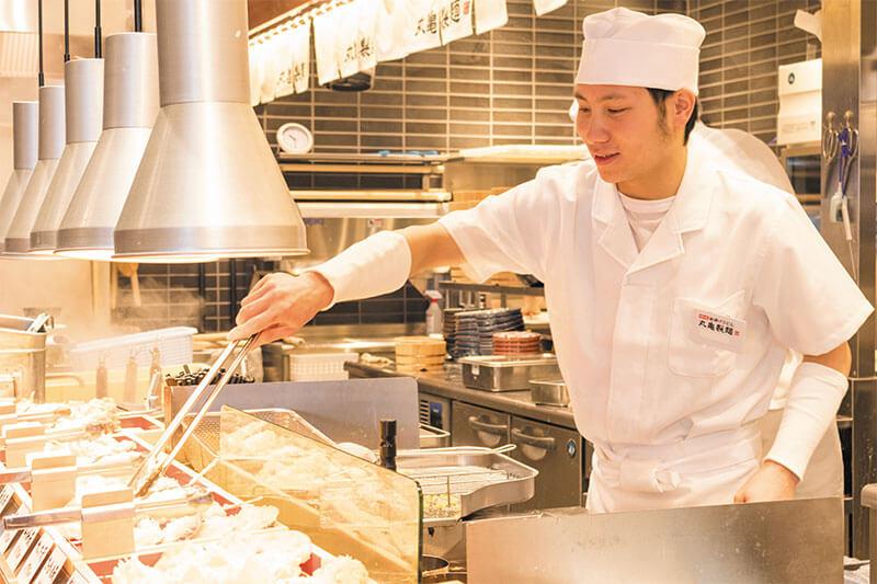 丸亀製麺の店員さんが天ぷらを置いている画像