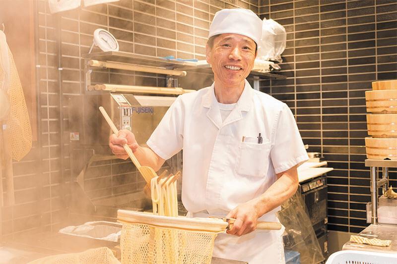 丸亀製麺のスタッフがうどんを茹でている画像