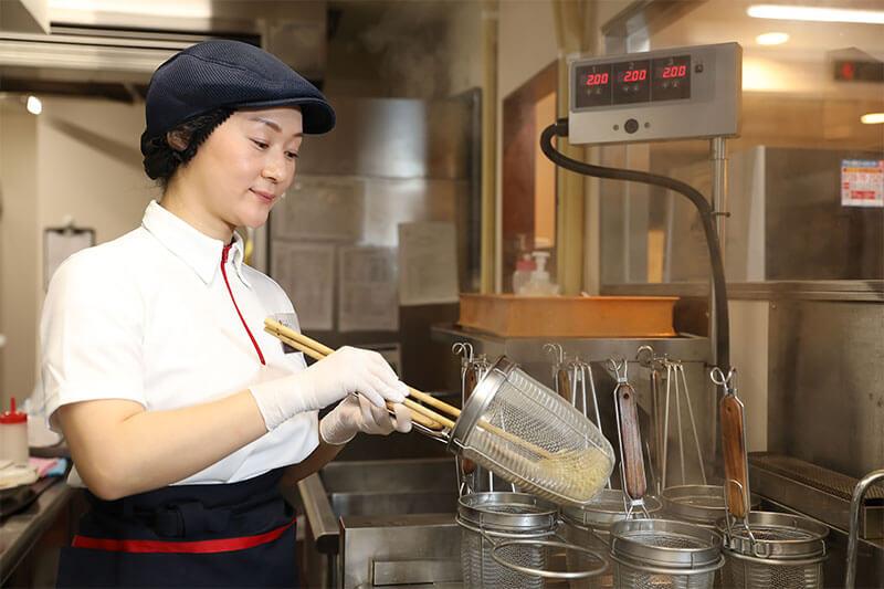 幸楽苑の店員さんがラーメンの麺の湯切りをしている画像