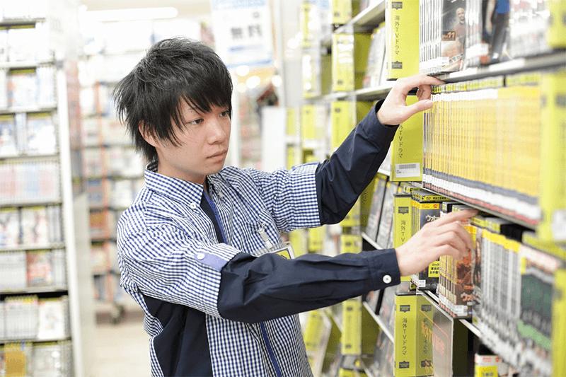 男性の店員さんが棚をチェックしている画像
