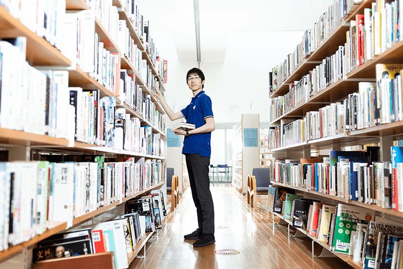 男性が本棚に本を戻している画像