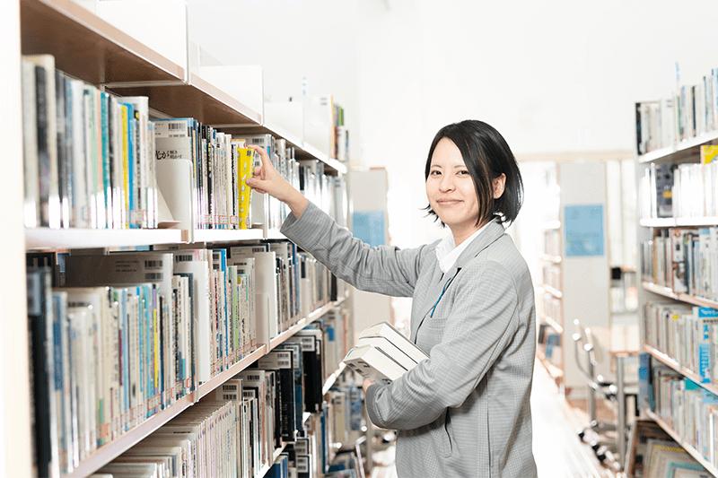 女性が本棚に本を戻している画像
