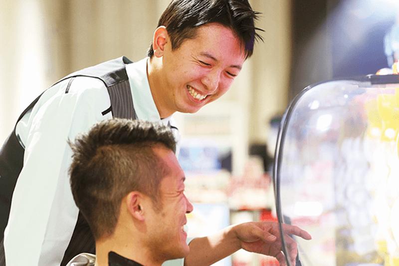 マルハンの男性店員さんがパチンコ中のお客様対応中の画像