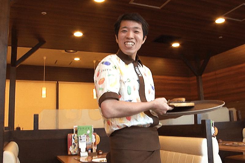 ココスの店員さんが料理を運んでいる画像