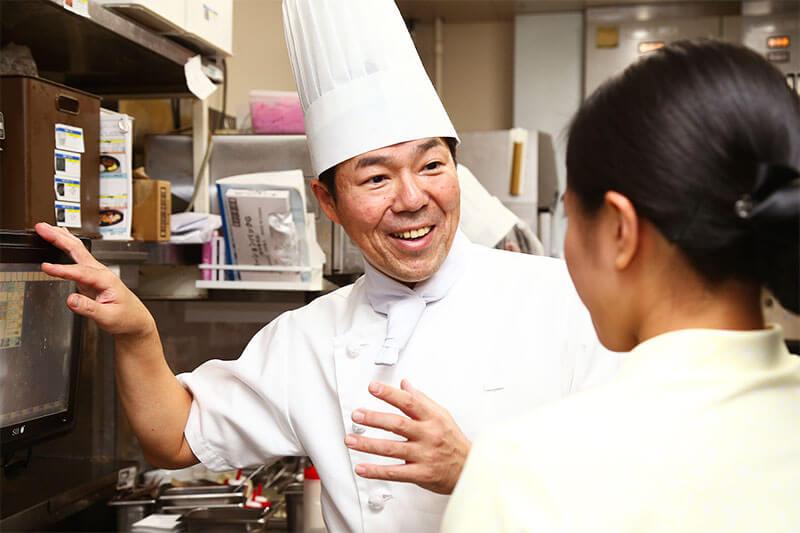 キッチンスタッフが店員とオーダーの確認をしている画像