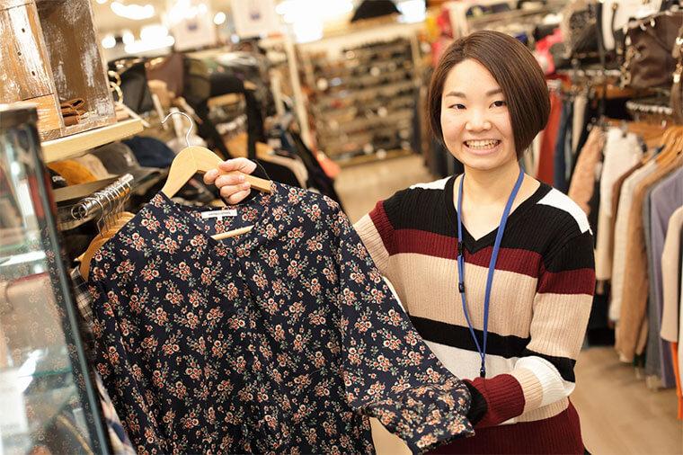 女性店員が洋服を進めている画像