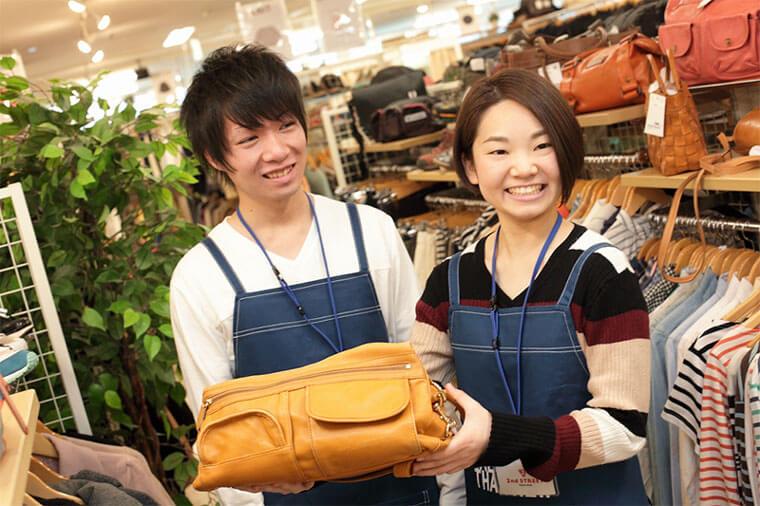女性店員と男性店員が商品のカバンを持っている写真