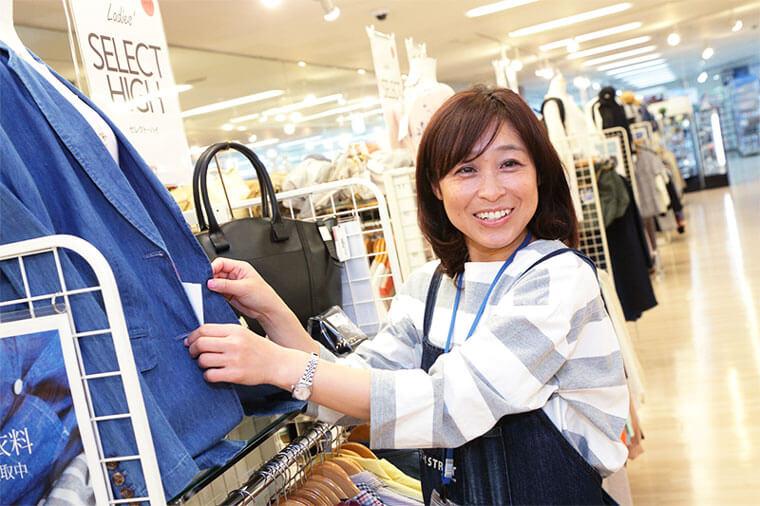 女性店員が商品のジャケットを直している写真