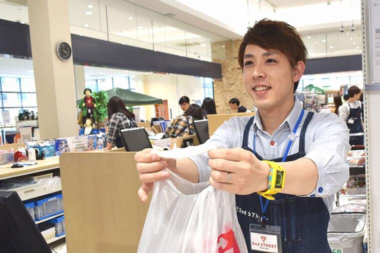 男性店員が会計後に商品を渡している写真