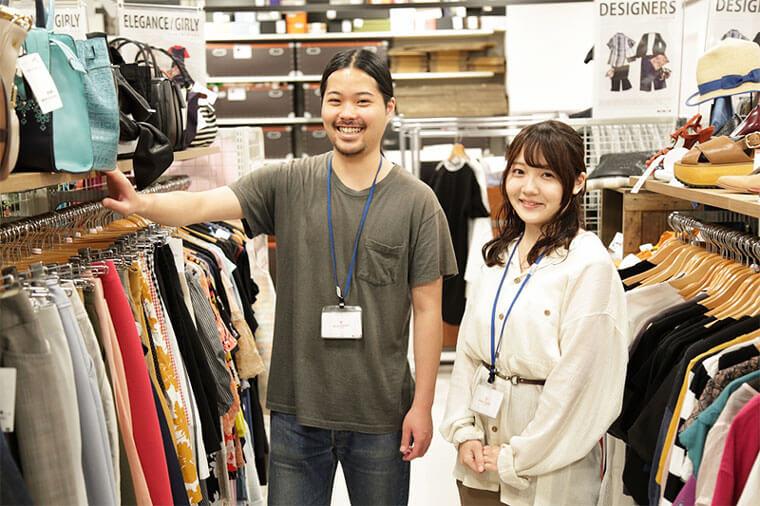 男性の店員と女性の店員が店の案内をしている写真