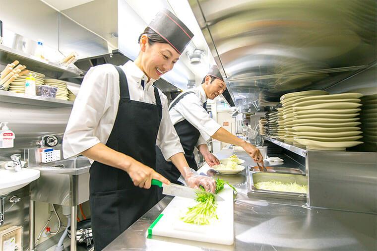 キッチンスタッフが野菜をきっている写真