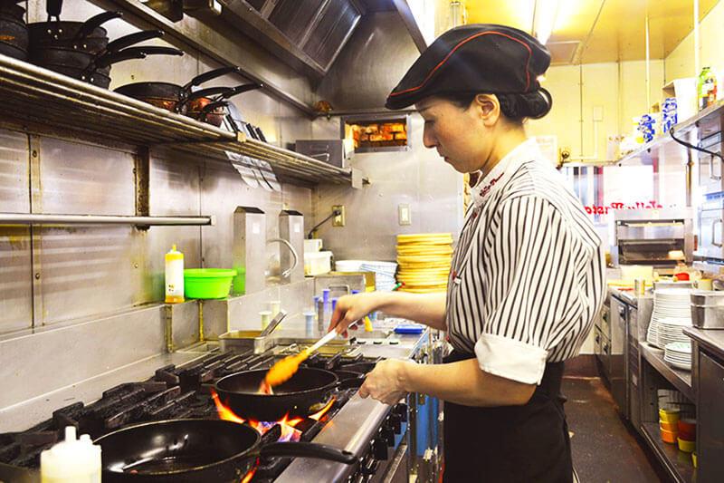 女性店員さんが料理を作っている写真