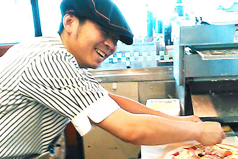 店員さんがピザを作っている写真