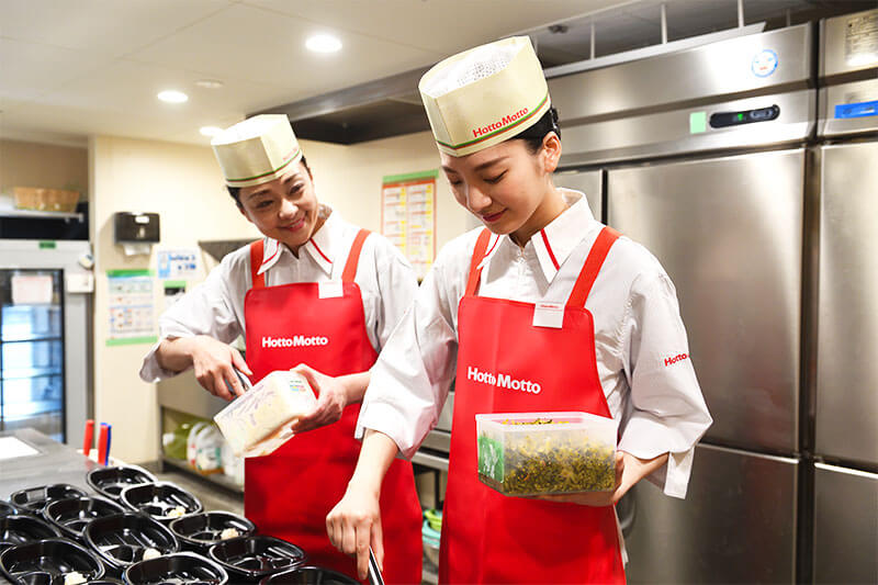 ほっともっとの厨房内で作業をする男性店員と女性店員の写真