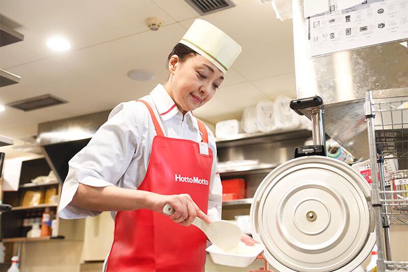 ほっともっとの厨房内でご飯をよそう女性店員の写真