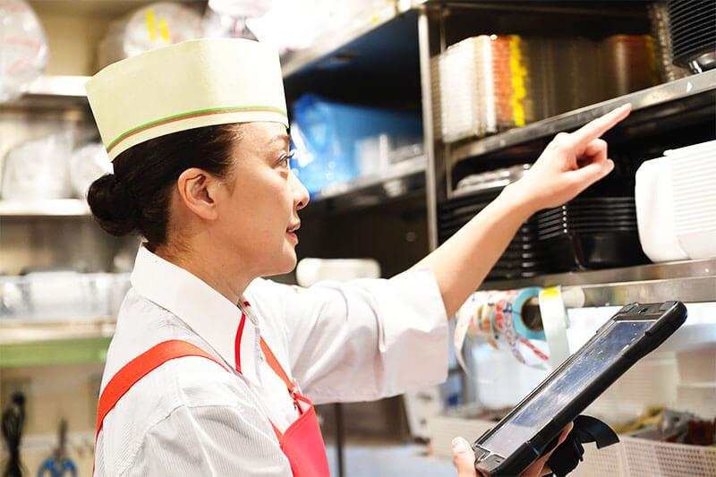 ほっともっと厨房内で備品チェックをする女性店員の写真