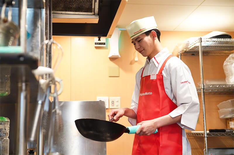 ほっともっとの厨房内で調理する男性店員の写真